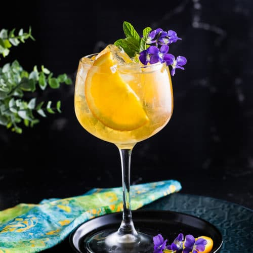 Spring Bourbon Spritz with orange slice and mint as garbage, served over ice in a large wine glass.