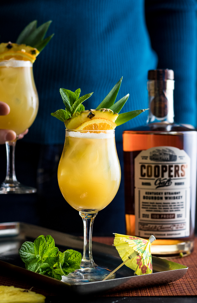 Whiskey Tiki Sour in two wine glasses with pineapple spear garnish, pineapple, orange and mint
