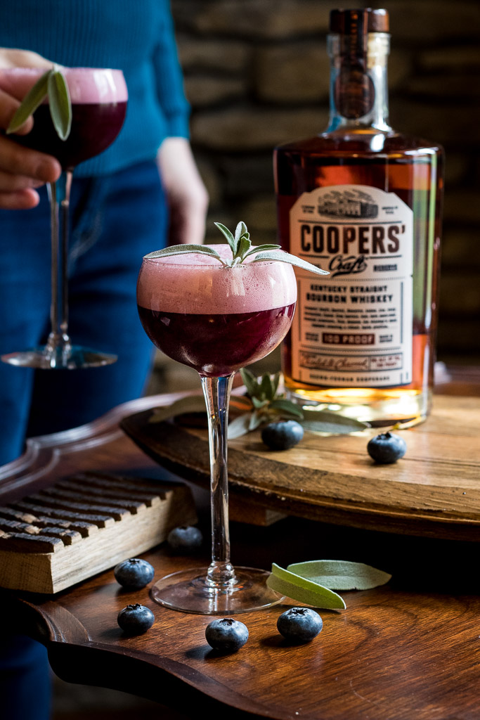 Coopers' Craft Cocktail - Blueberry Sour with sage leaf garnish and a bottle of Coopers' Craft on a gold tray