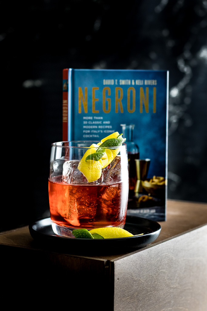 Oaxacan - a Negroni - Red cocktail on the rocks with lemon and lime peel and Negroni book in background