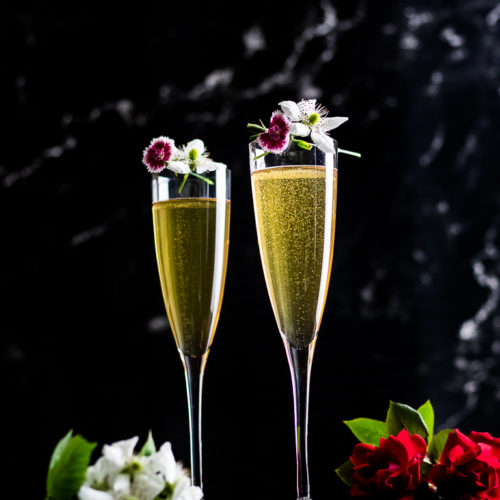Bourbon Mimosa - two champagne flutes with cocktail and fresh flower garnish