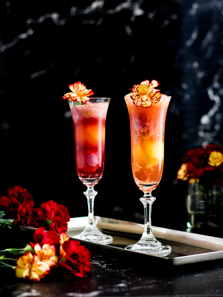 Bourbon and Bubbles Sorbet Cocktail for Mother's Day in two champagne flutes garnished with yellow and red mum