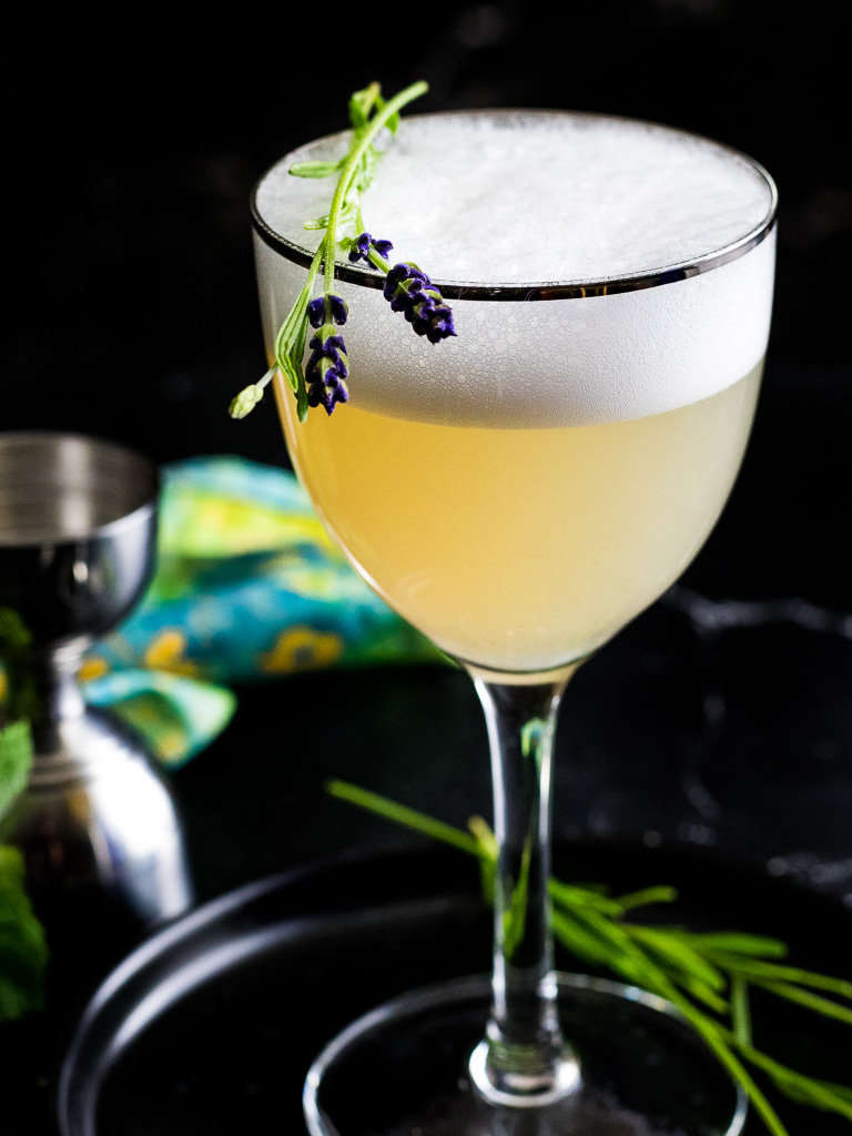 Lavender Gin Cocktail wi th foam in a Nick and Nora glass with fresh lavender garnish