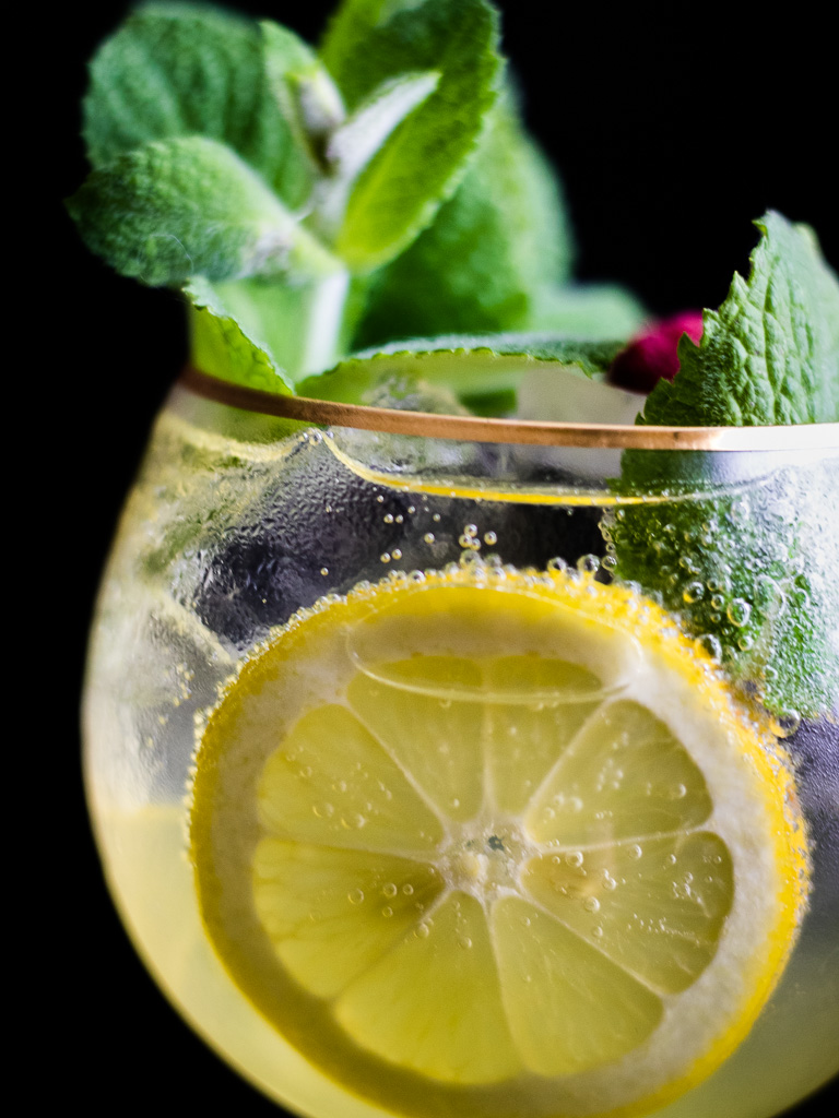 Limoncello Spritz in a wine glass with ice garnished with mint and lemon wheel, flowers