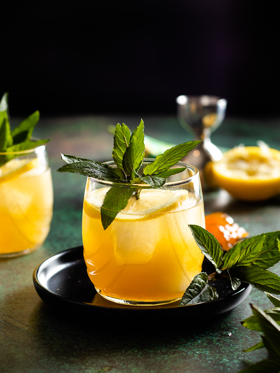bourbon limoncello cocktail with lemon wheel and mint garnish - 2 glasses, spoon of preserves