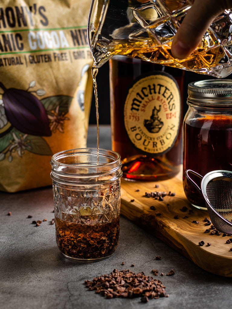 Making Chocolate Infused Whisey - pouring whiskey into a jar with cacao nibs, bottle of Michters Whiskey in the background