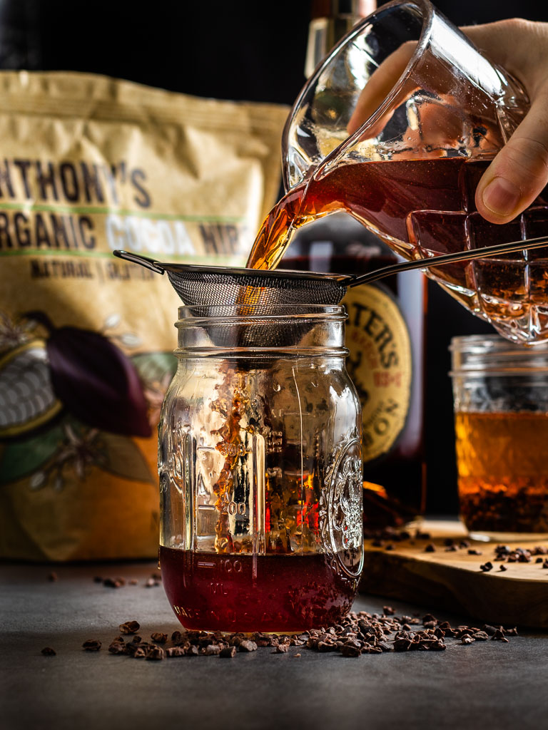 Making Chocolate Infused Whisey - pouring whiskey into a jar to strain cacao nibs, bottle of Michters Whiskey in the background