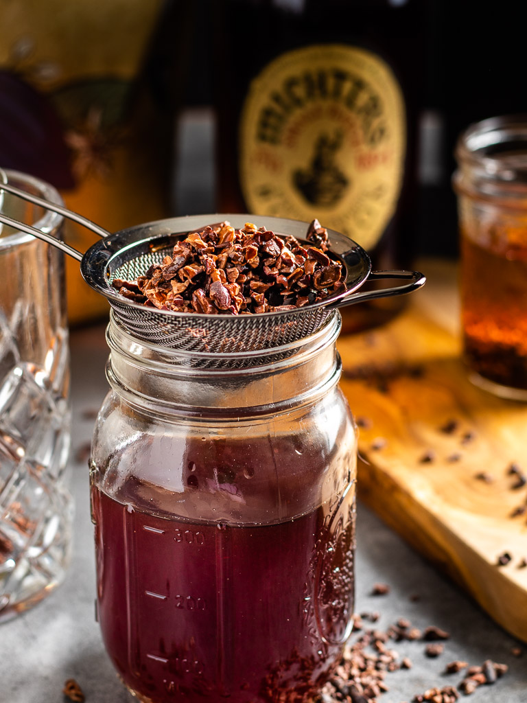 Making Chocolate Infused Whisey - strained whiskey in a jar strain full of cacao nibs, bottle of Michters Whiskey in the background