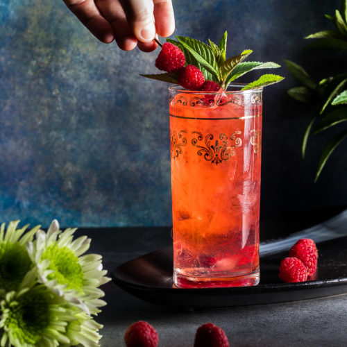 Raspberry Bourbon Buck cocktail in a tall collins glass with ice garnished with raspberries and min