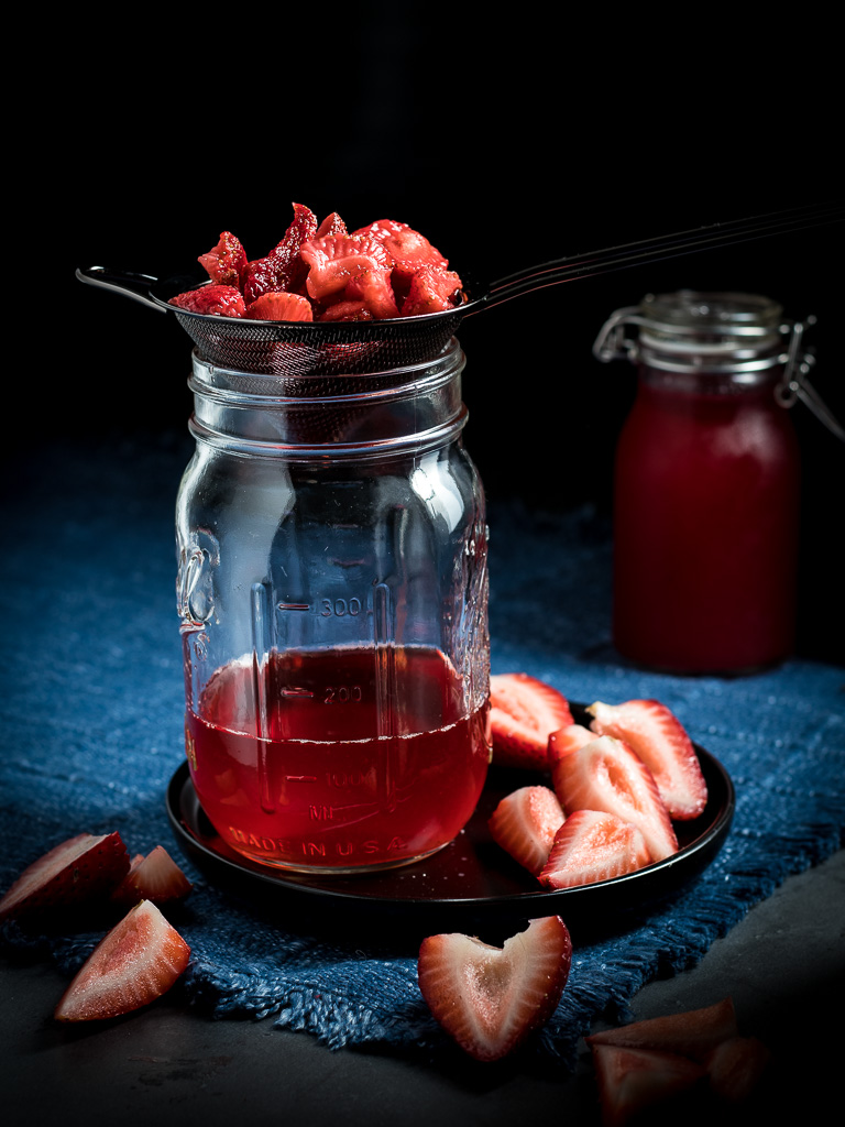 Homemade no cook strawberry simple syrup straining in a jar