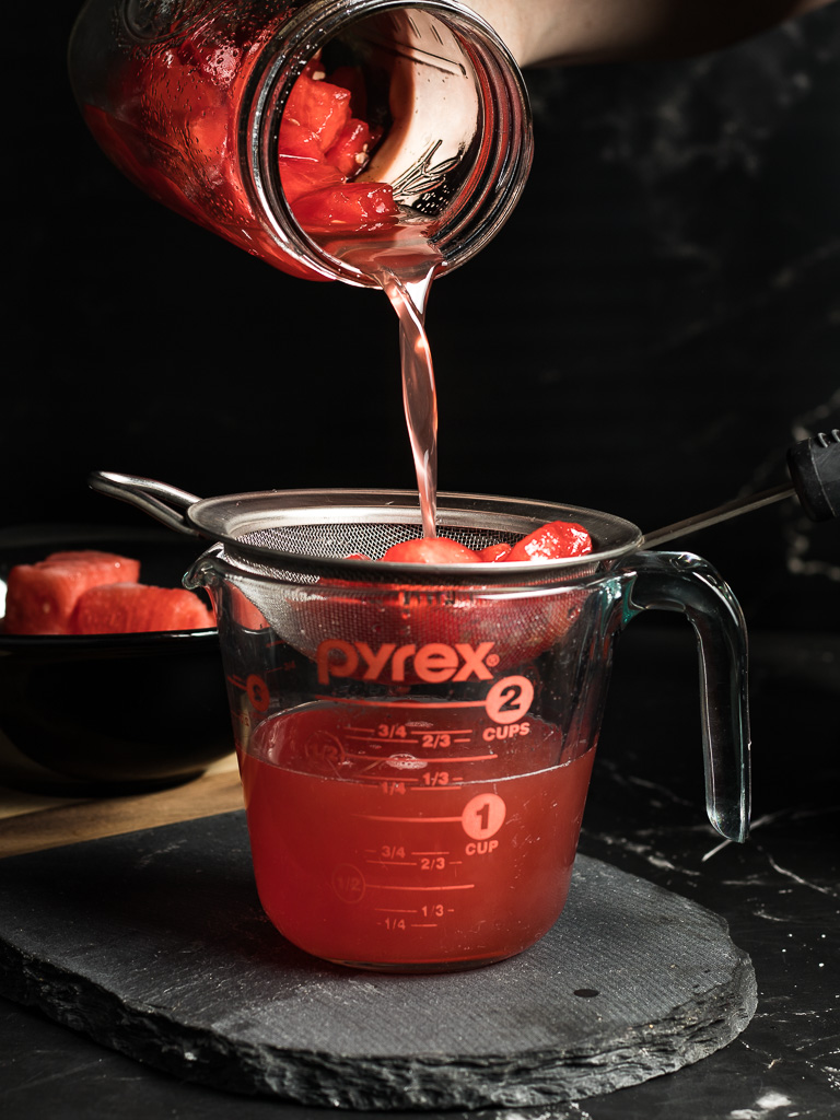 Watermelon Syrup for Cocktails - straining the syrup through a metal sieve into a measuring cup.