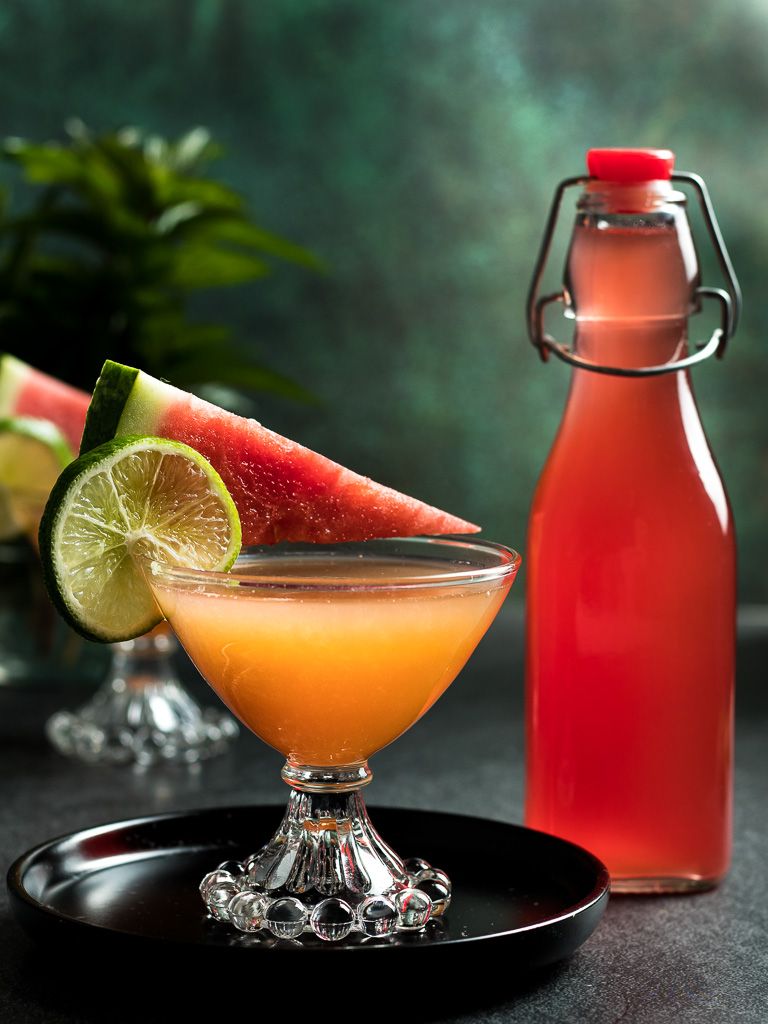 Watermelon Whiskey Cocktail in two coupe glasses garnished with a spear of watermelon and lime wheel