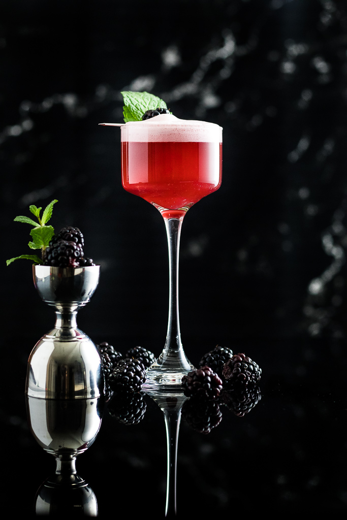 blackberry whiskey sour with foam and blackberry garnish in a coupe glass