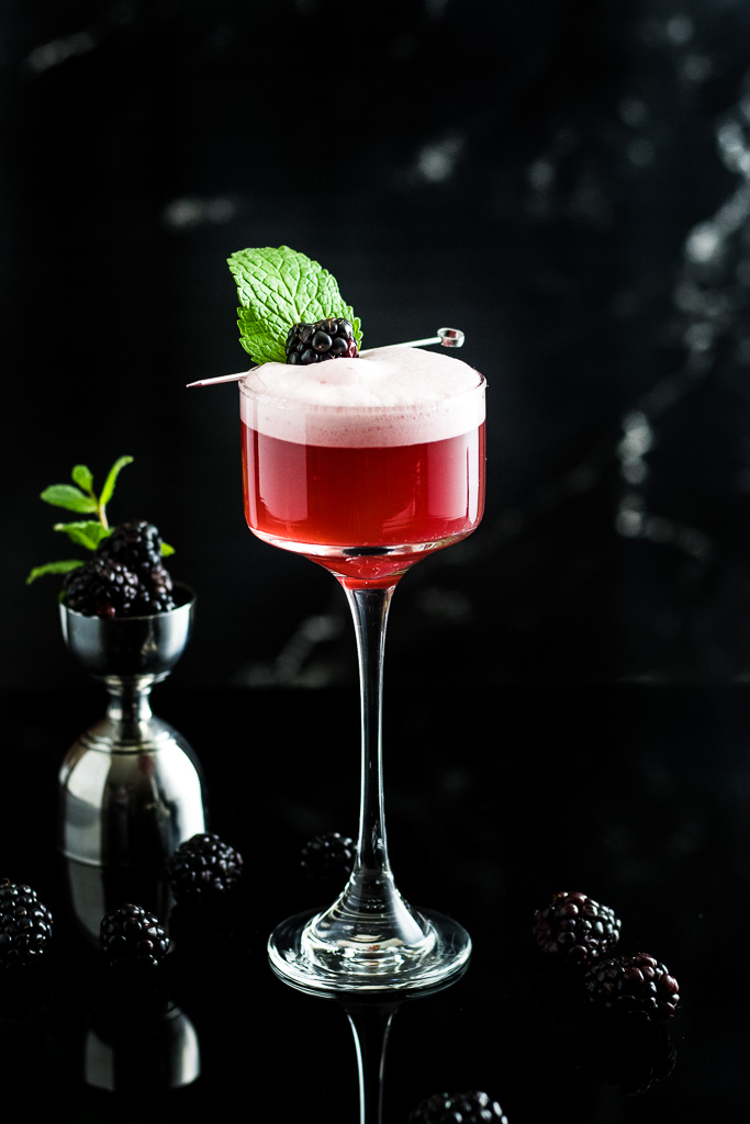 blackberry whiskey sour with foam and blackbery garnish in a coupe glass