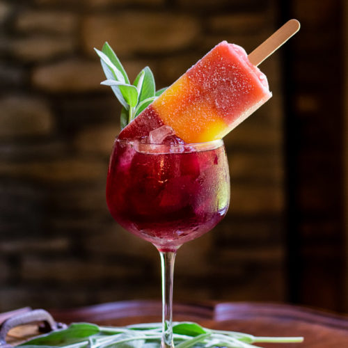 blueberry bourbon smash cocktail in tall wine glass with ice and topped with a sorbet popsicle and garnished with fresh sage