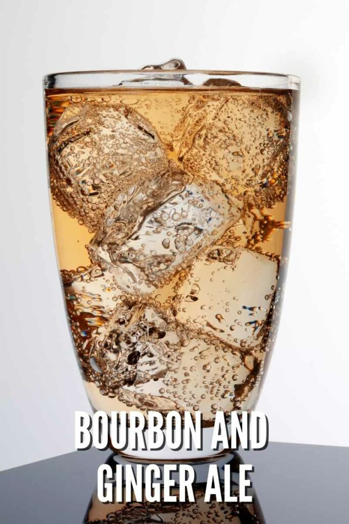 bourbon and ginger ale in tall glass over ice in front of white background