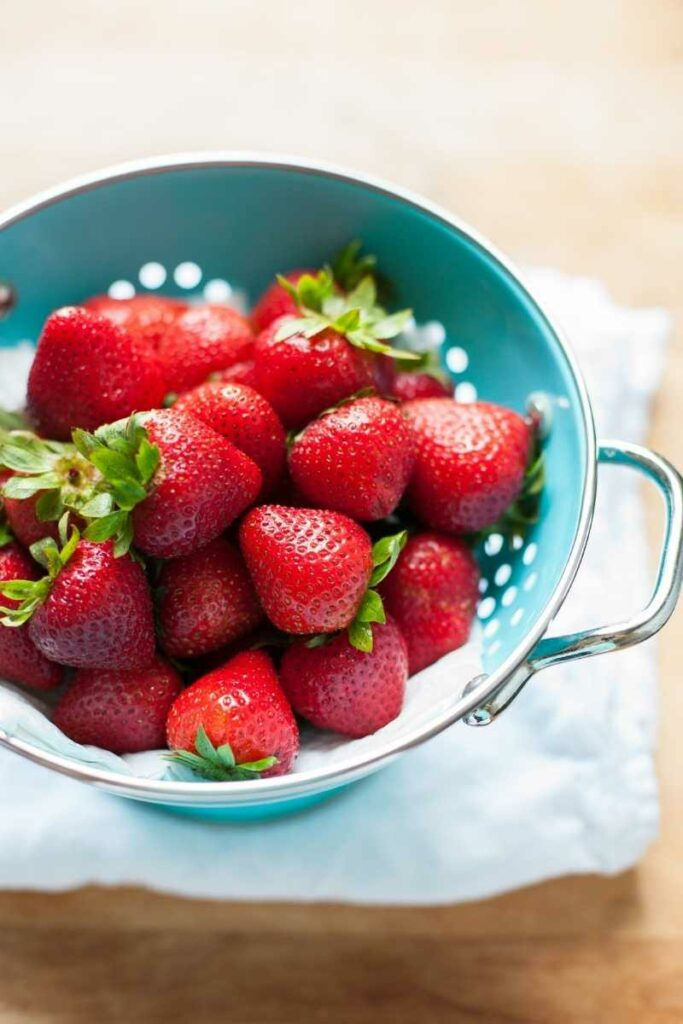 strawberries in a blue strainer on a towel