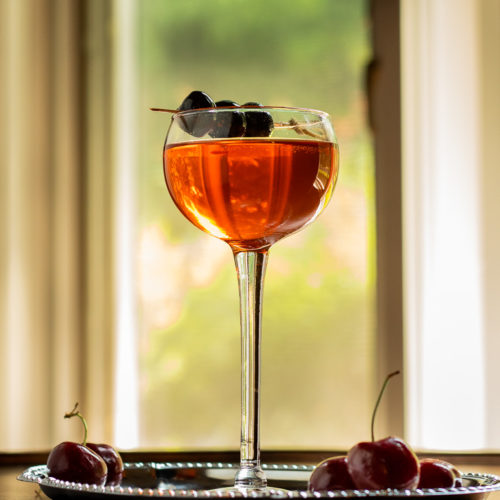 Aperol Manhattan - Little Italy in a coupe glass with a cherry garnish