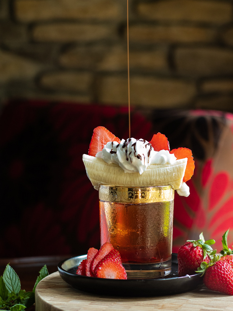 Banana Boulevardier with banana, whipped cream, strawberries and chocolate drizzle on top