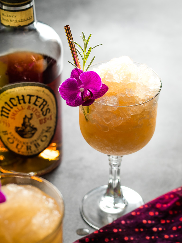 Lavender Lemon Bourbon Slushies - two in coupe glasses with lavender and flower garnish and bottles of whiskey and limoncello