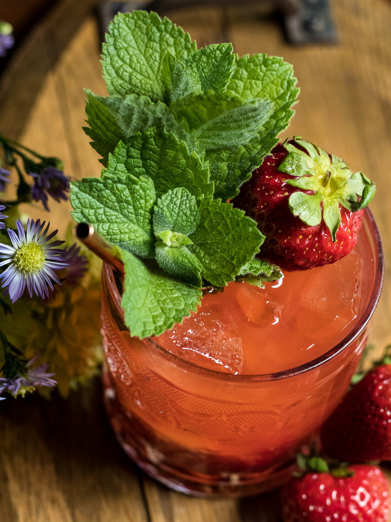 Strawberry whiskey smash in a rocks glass on a wooden tray with flowers and strawberries