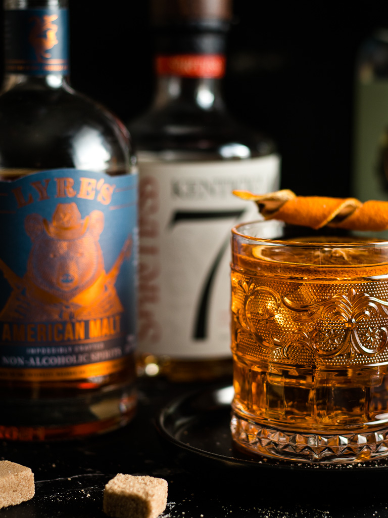 Non-Alcoholic Whiskey Alternatives for Whiskey Mocktails - Bottles of Lyre's, Seedlip Spice, Ritual Zero Proof and Kentucky 74 and a cocktail