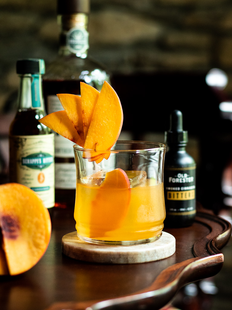 Peach Old Fashioned with bitters, peach slice and bourbon bottle behind it