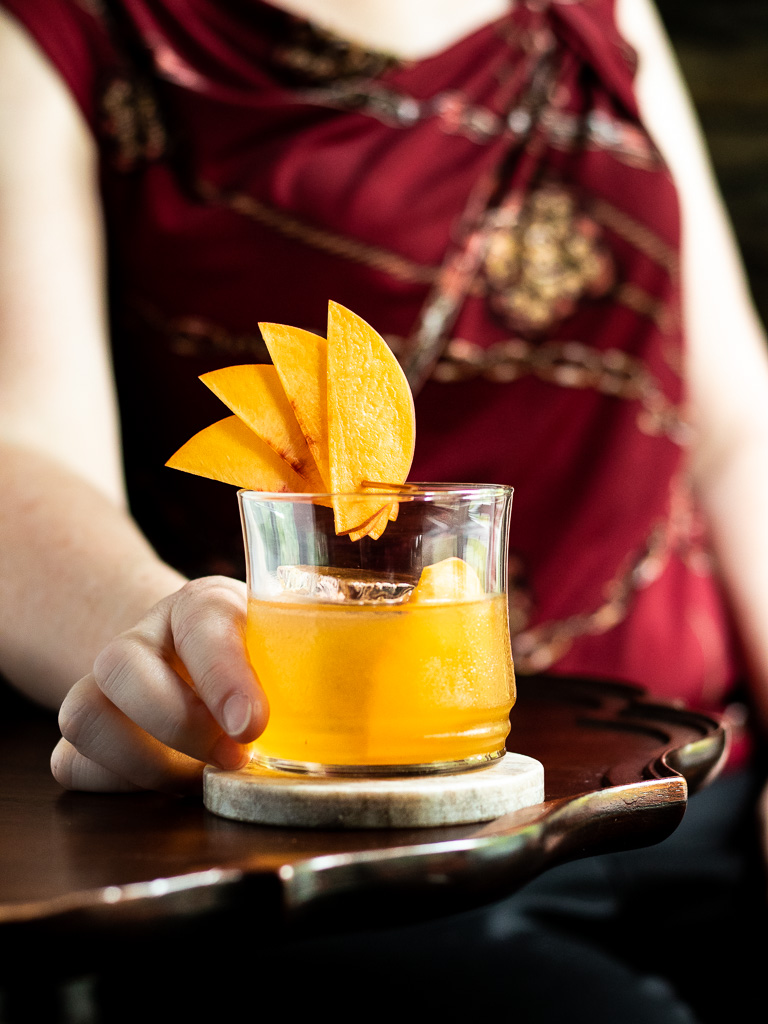 Peach Old Fashioned with woman holding the glass