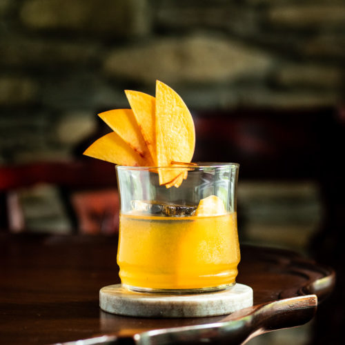 Peach Old Fashioned on a table with a peach fan garnish