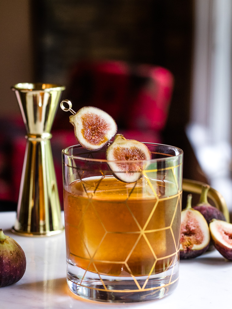 Fig Old Fashioned on a tray with fresh figs and jigger, garnished with fresh fig