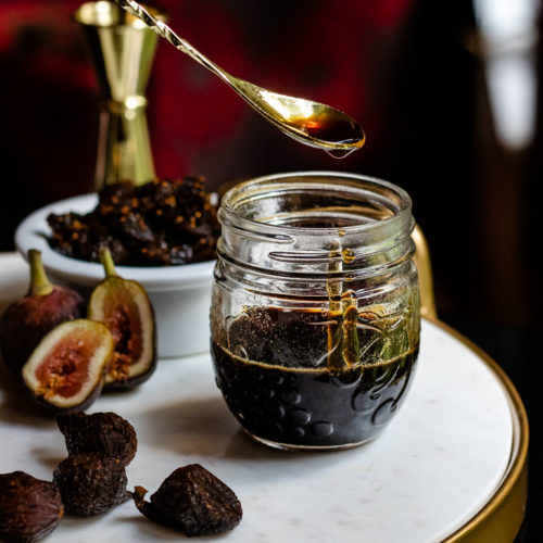 Homemade Fig Syrup in a jar with dried and fresh figs on a tray