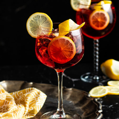 Negroni and Tonic in a wine glass garnished with a lemon wheel and lemon twist