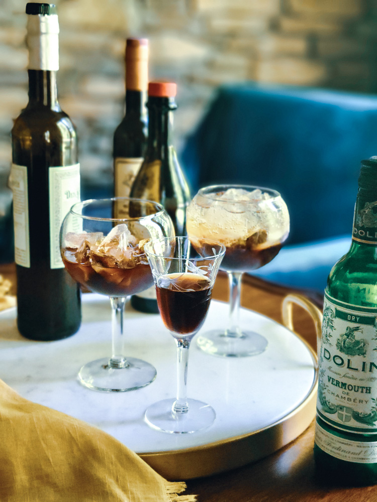 Vermouth lab - three wine glasses with vermouth surrounded by vermouth bottles